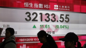 People walk past an electronic stock board showing the Hang Seng Index at a bank in Hong Kong, Friday, Jan. 19, 2018. (AP Photo/Kin Cheung)