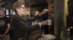 Ontario Premier Kathleen Wynne makes tea at a Toronto coffee shop, on Jan. 30, 2014. (Chris Young / THE CANADIAN PRESS)