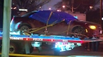 A vehicle covered in tarp is towed away from a scene in Etobicoke where a gunman opened fire on four occupants sitting inside it, killing two and critically injuring two others.