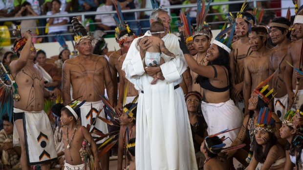 Pope Francis caresses a child as he arrives in a coliseum in Puerto Maldonado, the city considered a gateway to the Amazon in the Madre de Dios province, Peru, to meet with several thousand indigenous people in the first full day of the pontiff's visit to Peru, Friday, Jan. 19, 2018. (L'Osservatore Romano Vatican Media/Pool Photo)