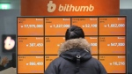 In this Tuesday, Jan. 16, 2018, file photo, a man watches a screen showing the prices of bitcoin at a virtual currency exchange office in Seoul, South Korea. (AP Photo/Ahn Young-joon)