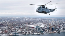 A CH-124 Sea King helicopter flies over the harbour in Halifax on Friday, Jan.19, 2018. The half-century-old helicopters will see their last official East Coast flight on Jan. 26, 2018 and eventually replaced with the CH-148 Cyclone. THE CANADIAN PRESS/Andrew Vaughan