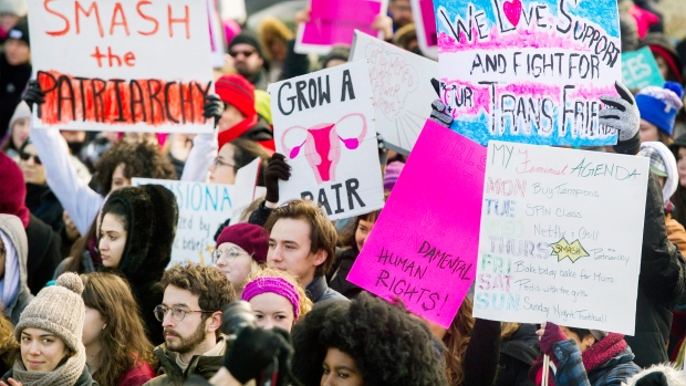 People hold up signs during a women's march in Montreal, Saturday, January 20, 2018. THE CANADIAN PRESS/Graham Hughes