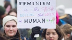 A woman holds up a sign during a women's march in Montreal, Saturday, January 20, 2018. THE CANADIAN PRESS/Graham Hughes