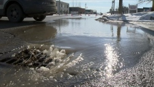 Water rushes into a drain on Otonabee Drive in Kitchener following a nearby water main break.