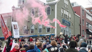 Pink flares are lit during a Women's March in solidarity with women and human rights groups across the world in Halifax on Saturday, January 20, 2018. (THE CANADIAN PRESS/Darren Calabrese)