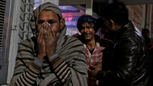 Relatives of firecracker factory fire victim, wail at a hospital on the outskirts of New Delhi, India, early Sunday, Jan. 21, 2018. A big fire broke out at a firecrackers factory on the northern outskirts of the Indian capital on Saturday, killing at least 17 workers, a fire official said. (AP Photo/Altaf Qadri)