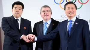 International Olympic Committee, IOC, President Thomas Bach, center, from Germany shakes hands with North Korea's Olympic Committee President and sports minister Kim Il Guk, left, and South Korea's Sports Minister Do Jong-hwan, right, as they arrive for the North and South Korean Olympic Participation Meeting at the IOC headquarters in Pully near Lausanne, Saturday, Jan. 20, 2018. (Laurent Gillieron/Keystone via AP)