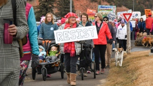 Protesters hold signs as hundreds gather for the second Women's March in Carbondale, Colo., on Saturday, Jan. 20, 2018, on the anniversary of U.S. President Donald Trump's inauguration. (Chelsea Self/Glenwood Springs Post Independent via AP)