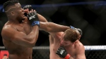 Stipe Miocic, right, lands a right hand against Francis Ngannou during a heavyweight championship mixed martial arts bout at UFC 220, early Sunday, Jan. 21, 2018, in Boston. (AP Photo/Gregory Payan)
