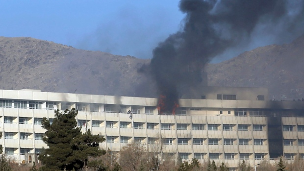 Men try to escape from a balcony of the Intercontinental Hotel after an attack in Kabul, Afghanistan, Sunday, Jan. 21, 2018. (AP Photo/Rahmat Gul)