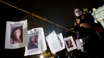 This Nov. 1, 2017 file photo, a woman embraces a girl next to images of murdered women following a Day of the Dead march calling for justice for victims of femicide, in Mexico City. (AP Photo/Rebecca Blackwell)
