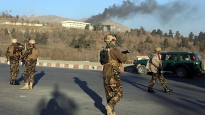 Afghan security personnel stand guard as black smoke rises from the Intercontinental Hotel after an attack in Kabul, Afghanistan, Sunday, Jan. 21, 2018. (AP Photo/Rahmat Gul)