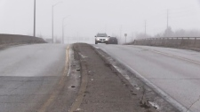 A vehicle makes its way over the Franklin Boulevard bridge in Cambridge on a foggy day.