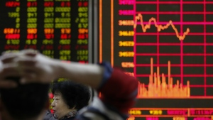 A woman chats with her friend as they monitor stock prices at a brokerage house in Beijing, Monday, Jan. 22, 2018. (AP Photo/Andy Wong)