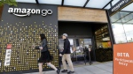 People walk past an Amazon Go store in Seattle on  Thursday, April 27, 2017. (AP Photo/Elaine Thompson, File)