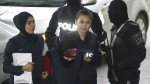 Indonesian Siti Aisyah, second left, is escorted by police as she arrives for court hearing at Shah Alam court house in Shah Alam, Malaysia, Monday, Jan. 22, 2018. (AP Photo/Sadiq Asyraf)