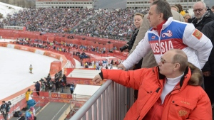 Russian President Vladimir Putin, foreground, and Vitaly Mutko watches downhill ski competition of the 2014 Winter Paralympic, on March 8, 2014. (RIA-Novosti, Alexei Nikolsky, Presidential Press Service)