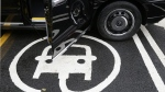 The electric car recharging sign, as a new TX Cab London taxi is parked at a charging station during a media opportunity at a Shell gas station on Holloway road, in London, Wednesday Oct. 18, 2017, 2017. (AP / Tim Ireland)