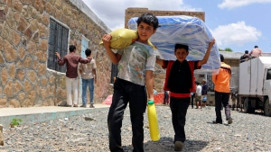 In this May 9, 2015 photo, boys carry relief supplies to their families who fled fighting in the southern city of Aden, in Taiz, Yemen. Saudi Arabia said Sunday, Jan. 21, 2018, that the coalition it is leading in Yemen will provide $1.5 billion in new humanitarian aid for international relief organizations working in the impoverished country. (AP / Abdulnasser Alseddik)