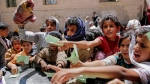 In this April 13, 2017, file photo, Yemenis present documents in order to receive food rations provided by a local charity, in Sanaa, Yemen. (AP / Hani Mohammed, File)