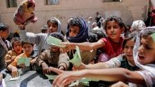 Yemenis present documents in order to receive food