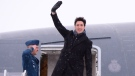 Canadian Prime Minister Justin Trudeau waves from the steps of his plane as he departs Ottawa for Davos, Switzerland for the annual World Economic Forum on Monday, January 22, 2018. THE CANADIAN PRESS/Paul Chiasson