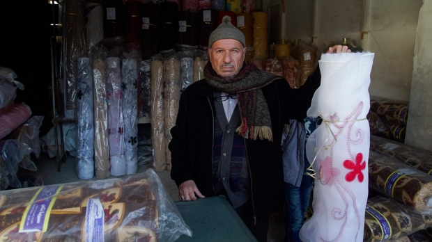In this picture taken Sunday, Jan. 21, 2018, Mahmoud Mimeh, textile shops owner at the old market, poses for a picture inside his shop in the old city of Aleppo, Syria. (AP Photo/Mstyslav Chernov)