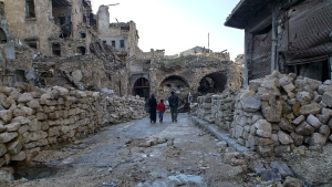 In this picture taken Sunday, Jan. 21, 2018, a Syrian family walks through the destruction of the old market in the old city of Aleppo, Syria. (AP Photo/Mstyslav Chernov)