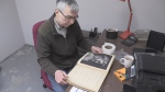A man sits at a desk with a very old book he's restoring