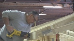 A worker uses a hand held saw on a roof truss