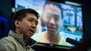 Wilfred Wong speaks about his brother Alfred Wong, 15, seen on a television, who was an innocent victim of an alleged gang shooting, during a Vancouver Police news conference in Vancouver, B.C., on Monday January 22, 2018. Wong was hit by a stray bullet as his family was driving in Vancouver on January 13. THE CANADIAN PRESS/Darryl Dyck