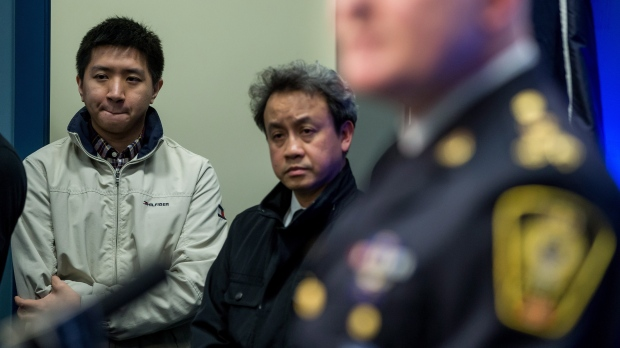 Wilfred Wong, back left, whose brother Alfred Wong, 15, was an innocent victim of an alleged gang shooting, and Pastor Caleb Choi listen as Vancouver Police Chief Adam Palmer speaks during a news conference in Vancouver, B.C., on Monday January 22, 2018. (Darryl Dyck/THE CANADIAN PRESS)