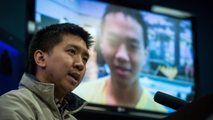 Wilfred Wong, left, speaks about his brother Alfred Wong, 15, seen on a television, who was an innocent victim of an alleged gang shooting, during a Vancouver Police news conference in Vancouver, B.C., on Monday January 22, 2018. THE CANADIAN PRESS/Darryl Dyck