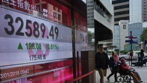 People walk past a bank electronic board showing the Hong Kong share index at Hong Kong Stock Exchange Tuesday, Jan. 23, 2018. (AP Photo/Vincent Yu)
