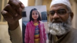 Mohammed Amin shows a picture of his seven year-old daughter, Zainab Ansari in Kasur, Pakistan on Thursday, Jan. 18, 2018. (AP Photo/B.K. Bangash)