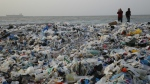 A man takes photos of piles of garbage washed on shore after an extended storm battered the Mediterranean country at the Zouq Mosbeh costal town, north of Beirut, Lebanon on Monday, Jan. 22, 2018. (AP Photo/Hussein Malla)