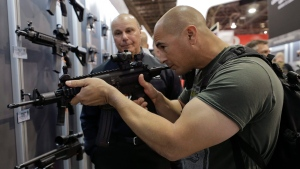In this Jan. 14, 2014, file photo, John Montenegro of the Los Angeles Police Department S.W.A.T. team, examines a Sig Sauer MPX-K short barrel submachine gun during the Shooting Hunting and Outdoor Trade Show in Las Vegas. (AP Photo/Julie Jacobson, file)