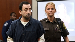 Larry Nassar is escorted into the courtroom, Thursday, Jan. 18, 2018, in Lansing, Mich., during the fourth day of sentencing for former sports doctor Larry Nassar, who pled guilty to multiple counts of sexual assault. (Dale G. Young/Detroit News via AP)