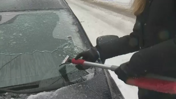 Kelly Craig scrapes ice off her car in Montreal following freezing rain on Jan. 23, 2018
