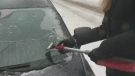 A Montreal woman scrapes ice off her car.