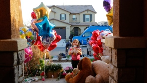 Neighbor Rilee Unger, 3, plays with a toy after dropping off a couple of her own teddy bears on the porch of a home where police arrested a couple on Sunday accused of holding 13 children captive in Perris, Calif., Thursday, Jan. 18, 2018. (AP Photo/Damian Dovarganes)
