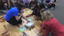 Students in a classroom gathered around what appears to be a robot they are coding