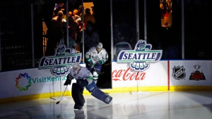 In this Jan. 9, 2018, photo, fans cheer at the ShoWare Center in Kent, Wash., about 20 miles south of Seattle, as Seattle Thunderbirds' Liam Hughes, left, and Nolan Volcan, right, take the ice at the start of a Western Hockey League game. (Ted S. Warren/AP Photo)