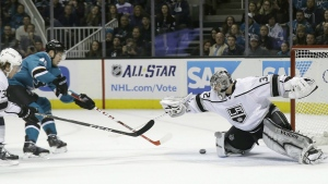 Los Angeles Kings goalie Jonathan Quick, right, stops a shot from San Jose Sharks center Tomas Hertl, centre, during the first period of an NHL hockey game in San Jose, Calif. on Saturday, Dec. 23, 2017. (AP Photo/Marcio Jose Sanchez)