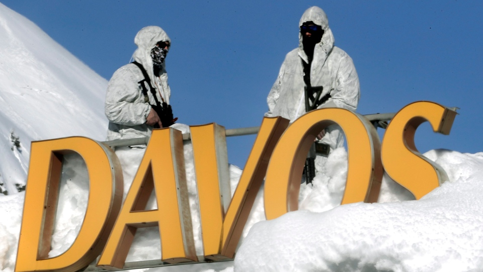 Armed Swiss police officers stand guard on the roof of a hotel near the congress center where the annual meeting of the World Economic Forum takes place in Davos, Switzerland, Wednesday, Jan. 24, 2018. (AP Photo/Markus Schreiber)