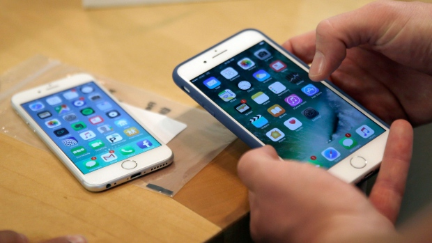 A Friday, Sept. 16, 2016 file photo of a customer setting up his new iPhone 7 Plus, right, as he switches from the iPhone 6 at the Apple Store on Michigan Avenue, Chicago, IL., during the release of the Apple iPhone 7. (AP Photo/Kiichiro Sato, File)