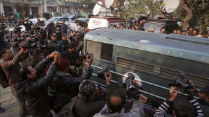 Surrounded by journalists and security forces, a prison van carrying Mohammad Imran, who is accused of the brutal killings of eight children in the eastern city of Kasur, arrives to a courthouse, in Lahore, Pakistan, Wednesday, Jan. 24, 2018. (AP / K.M. Chaudary)