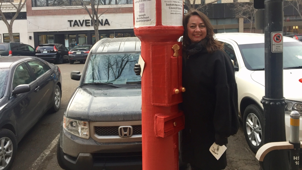 Artist Monique Martin stands by one of her red mailboxes in downtown Saskatoon. (Laura Woodward/CTV Saskatoon)