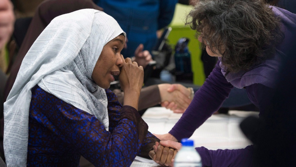 Idiatou Barry, left, wipes her eyes as she speaks with a woman during a gathering at the Centre Islamique de Quebec, marking the first anniversary of the mosque shooting, Saturday, January 27, 2018 in Quebec City. Barry lost her husband, Mamadou Tanou Barry, in the shooting,THE CANADIAN PRESS/Jacques Boissinot